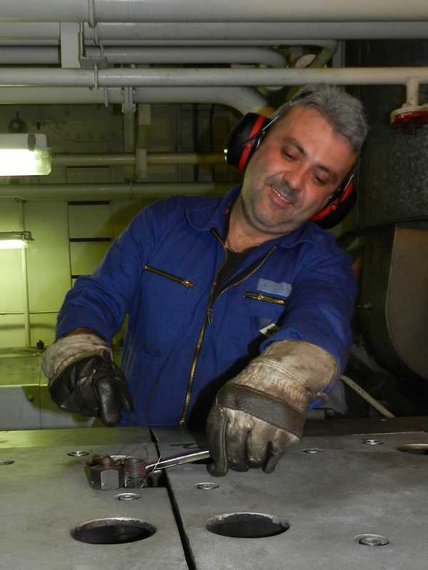 Ship mechanic performing installation works
